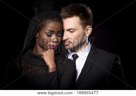 Close up portrait of romantic multi-ethnic couple on black background. Portrait of loving couple. Dark skinned woman with european man.