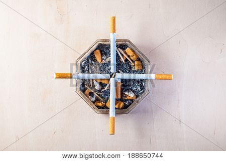 Filter cigarettes in a dirty ashtray with cigarette butts, conceptual photography representing health at gunpoint