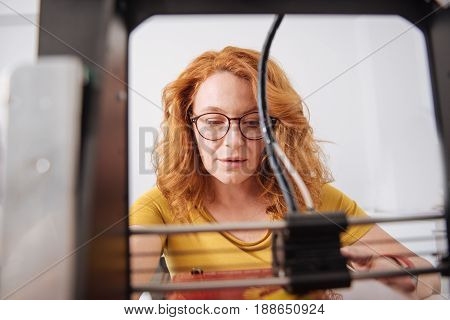 3d printing. Intelligent smart nice woman looking at the 3d printer and working with it while concentrating on her job