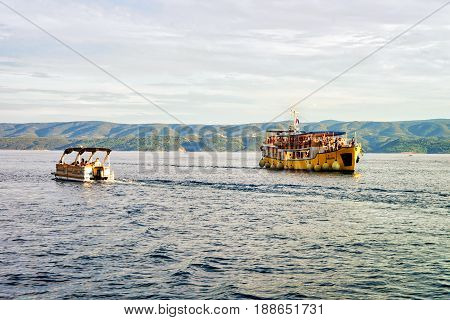 Excursion Ferry With Tourists And Motor Boat At Harbor Omis
