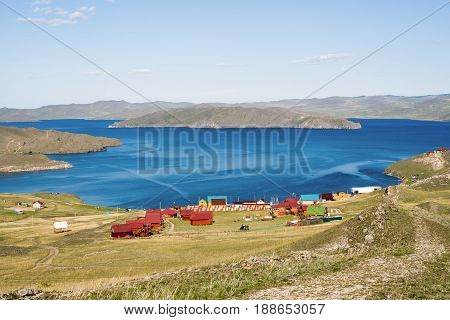 View of the strait between the mainland and Olkhon island, tourist centers near the village of Sahurta. In the distance Olkhon island. August. Lake Baikal, Siberia, Russia