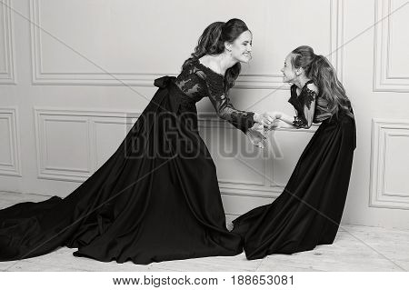 Mother and daughter hugging and looking at the camera. Happy loving family. Mother and daughter in beautiful long luxury blue dresses, makeup hairstyle. Fashion family portait. Generation relationship