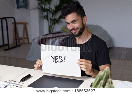 Graffiti artist in his urban art district studio confidently smiling confirms yes with thick bold marker on white background artisan paper smirks like a winner
