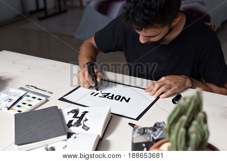 Handsome young millennial artist is hand writing a note with a thick bold black marker on blank white paper handwritten text NOPE businnes start up and refusal concept