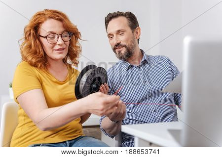 3d printer equipment. Professional nice 3d designer holding a filament coil and holding a string of filament while working with her male colleague