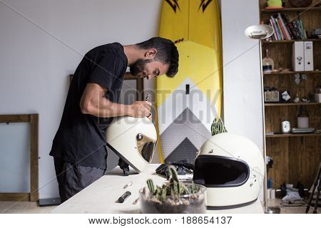 Handsome smiling artist decorates full face motorcycle helmet with thick oil brush and ink marker inside designer interior industrial loft or art studio in hip district