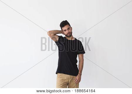 Smiling brutal spanish man with three day beard smirks and smiles into camera wears blank black t-shirt chino pants for summer season and friendship bracelet isolated on white mockup