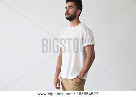Serius bearded male looks ahead with thinking face expression wears white simple blank t-shirt isolated on mockup ready for design