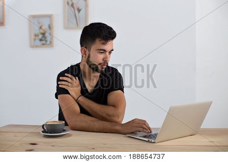Handsome young brutal man with muscular arms works on his laptop in cool district downtown cafe drinks cappuccino with latte art and types on computer surfing internet