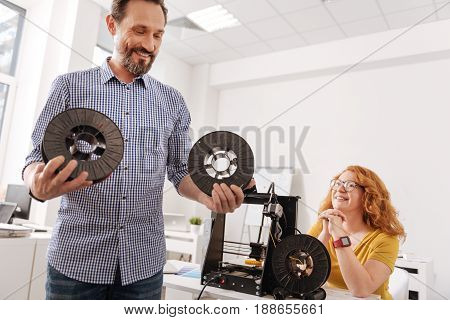 Modern way of printing. Happy positive delighted man holding the filament coils and looking at them while being in a great mood