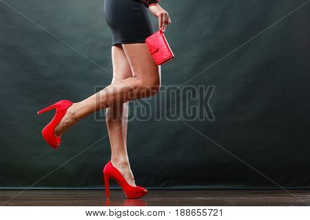 Celebration disco and evening fashion concept. Woman in black short dress red spiked shoes holding handbag purse part of body female legs in high heels on party floor