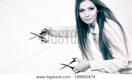 Cutting as a way of healthy strong hair. Girl barber with scissors ready to trimming. Female stylist holds trimmers prepared to haircut.