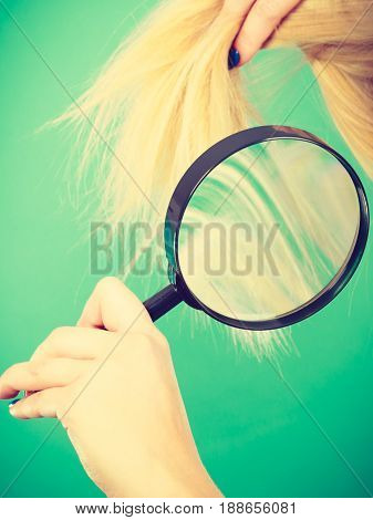 Woman Looking At Hair Through Magnifying Glass