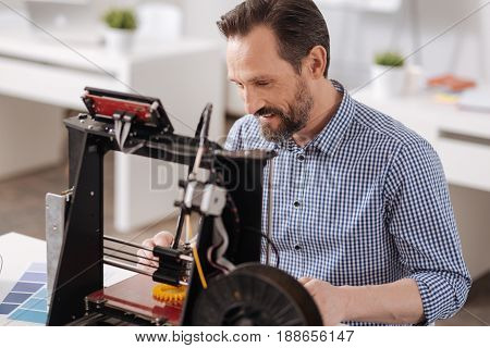 3d technology. Cheerful positive nice man sitting at the table and printing a 3d object while working as a 3d designer
