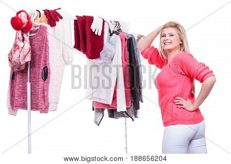 Young woman indecision in wardrobe home closet teen blonde girl choosing her warm fashion outfit on clothing rack. Picking winter autumn clothes shopping concept.