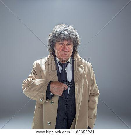 Senior police agent with a gun standing as detective or mafia boss. Studio shot on gray in retro stile
