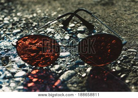 sunglasses with brown lenses and metallic spectacle frame on rough textured surface on asphalt grey background. Protective eyewear and fashion. Vision