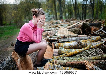 Beautiful Young Woman Sitting And Covering His Face With His Hands, On Stack Of Felled Tree Trunks I