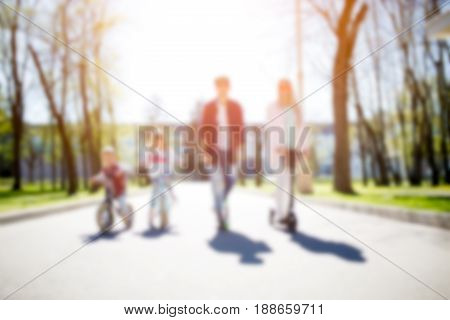 Blurred family photo on bicycles in park during day