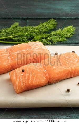 Two slices of salmon on a dark background with a place for text, with peppercorns and dill sprigs, with a place for text