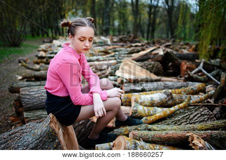Beautiful Young Woman Sitting On Stack Of Felled Tree Trunks In The Forest