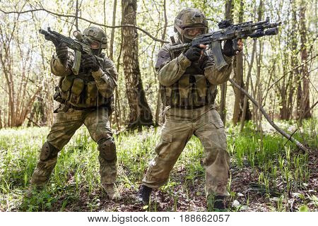 Two officers with machine guns in forest on reconnaissance