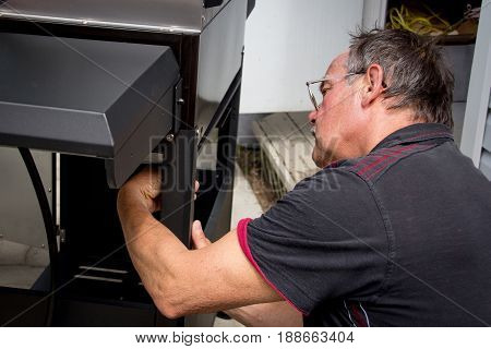60 years old repairman assembling barbecue grill appliance outdoor
