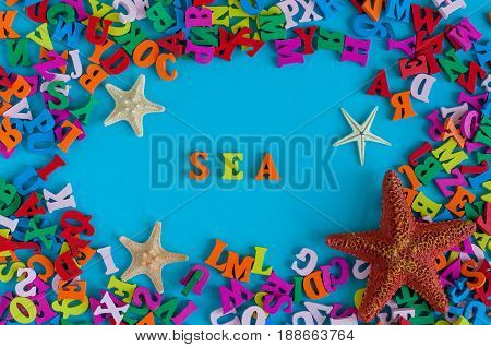 Sea - word composed of small colored letters. Summer vacation souvenir - starfish from tropical sandy ocean beach, holidays abroad - summertime top view concept.