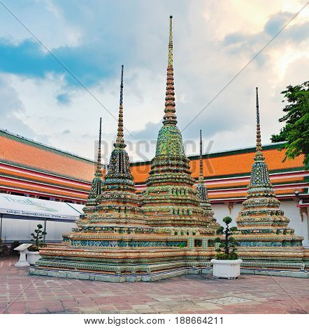 Bangkok, Thailand - December 7, 2015: Classical Thai architecture in Wat Pho public temple at stormy sunset cloudy sky, Bangkok, Thailand. Wat Pho known also as the Temple of the Reclining Buddha.