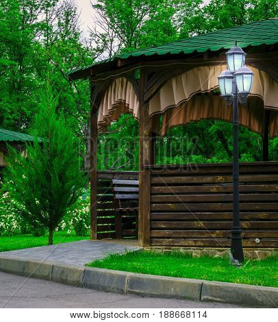 A magical and cozy place to relax a wooden gazebo near which a brightly lit street lamp around the beautiful green nature