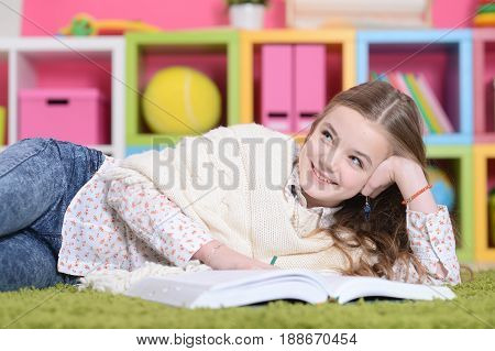 Portrait of cute little girl lying on green carpet