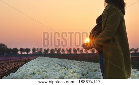 The stunning silhouette of a pregnant woman with her hands open hold the sunlight.