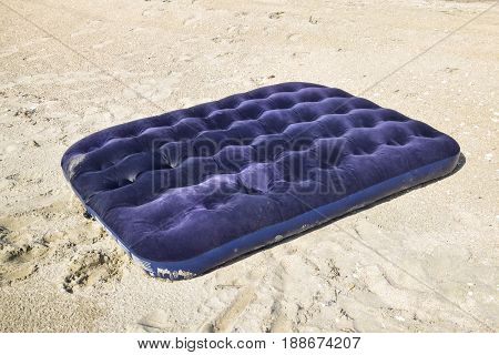 Blue inflatable mattress swimming in the pond. An inflatable mattress on the beach.