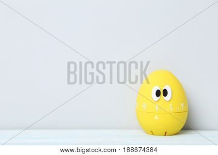 Yellow Egg Timer With Googly Eyes On A Grey Background