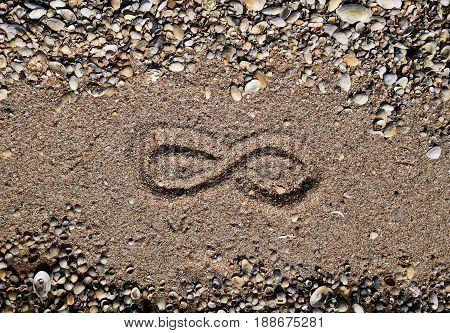The Sign Of Infinity On The Sea. Coastal Sand On The Beach. The Symbol Of Infinity