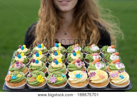 a girl holding a lot of cupcakes