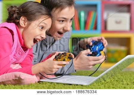 Excited brother and sister playing computer game with help of joysticks