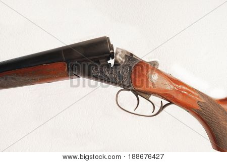 Detailed photo of a double-barrel rifle on a white background.