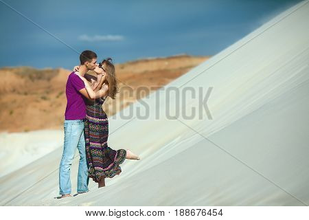tender lovers on romantic travel honeymoon vacation summer holidays romance. Young happy couple on the beach, caucasian woman and man embracing and kissing outdoors