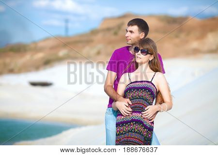 tender lovers on romantic travel honeymoon vacation summer holidays romance. Young happy couple on the beach with white sand, caucasian woman and man embracing outdoors