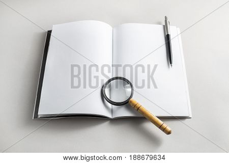 Photo of blank opened book magnifier and pencil on paper background. Stationery elements. Template for placing your design. Responsive design mockup.