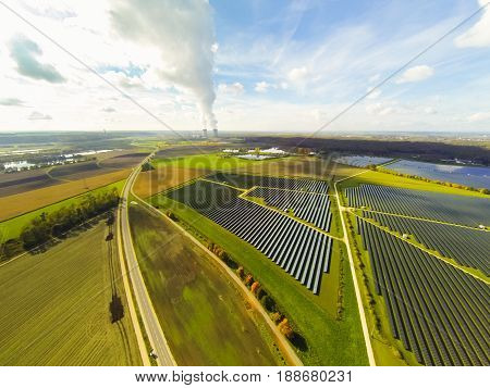 aerial view of solar power station, nuclear power plant in the background