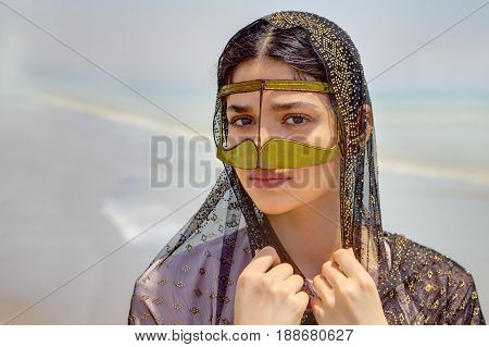 Close-up portrait of an Iranian girl in traditional Islamic dress of southern Iran.