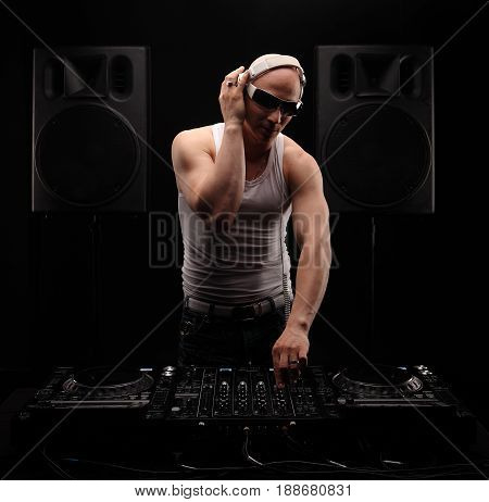 Club DJ with white headphones playing mixing music on turntable at party