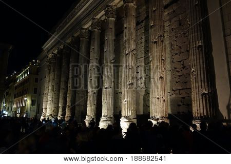 ROME ITALY - MAY 23 2017: People in front of the Temple of Hadrian at night built to deified Hadrian on the Campus Martius in 145 A.D.