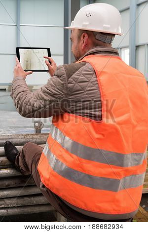 Construction supervisor checks the interior of a new warehouse being constructed with a digital tablet showing a map in his hand, wearing a safety helmet and vest