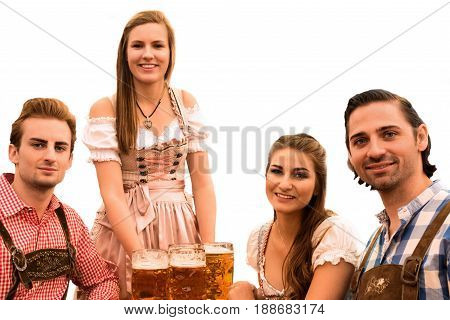Waitress delivers beers in tent with happy visitors in a beer tent at Munich Oktoberfest against white background