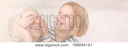 Smiling girl playing with her ill mother