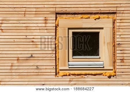 Wooden window. Foam window insulation on wooden construction. Building an eco-house. Heat insulation