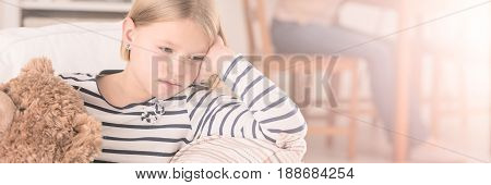 Girl sitting on a couch with teddy bear